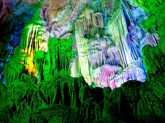 Stalactites inside Reed Flute Cave illuminated by colored lighting