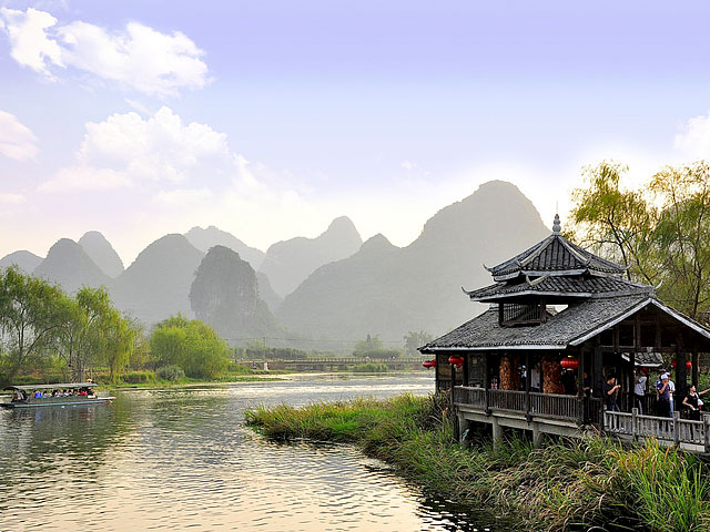 Classic tranquil scenery of Yangshuo town with ancient-style house by Li River and Karst landscape as background