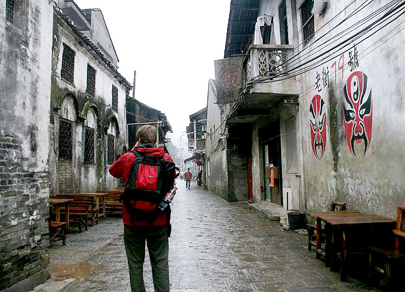 A tourist is exploring the ancient archetectures of Xingping ancient town
